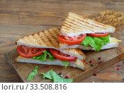 Купить «Sandwich with tomatoes, cheese and ham on a dark, wooden background», фото № 33508816, снято 8 апреля 2020 г. (c) Марина Володько / Фотобанк Лори