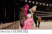 Купить «happy family at outdoor skating rink in winter», видеоролик № 33509332, снято 22 марта 2020 г. (c) Syda Productions / Фотобанк Лори