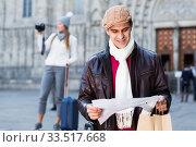 Купить «Male tourist standing with map», фото № 33517668, снято 18 ноября 2017 г. (c) Яков Филимонов / Фотобанк Лори