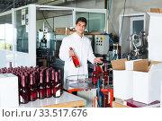 Купить «cheerful man employee standing in final section of wine production on factory», фото № 33517676, снято 21 сентября 2016 г. (c) Яков Филимонов / Фотобанк Лори