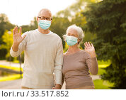 senior couple in protective medical masks at park. Стоковое фото, фотограф Syda Productions / Фотобанк Лори