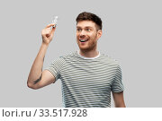 Купить «smiling young man holding lighting bulb», фото № 33517928, снято 21 марта 2020 г. (c) Syda Productions / Фотобанк Лори