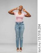 Купить «african woman in headphones listening to music», фото № 33518204, снято 26 января 2020 г. (c) Syda Productions / Фотобанк Лори