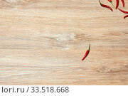 Single pod of red chili pepper lies on a wooden surface away from a group of other fruits. Стоковое фото, фотограф Евгений Харитонов / Фотобанк Лори