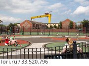 Great Britain, Belfast - Playground at the Dr Pitt Memorial Park and cranes of the shipyard H&W in East Belfast (2019 год). Редакционное фото, агентство Caro Photoagency / Фотобанк Лори