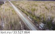 Купить «Вид сверху на движение автомобилей по автомагистрали через лес», видеоролик № 33527864, снято 2 апреля 2020 г. (c) Евгений Ткачёв / Фотобанк Лори