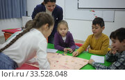 Young female teacher and happy schoolkids playing interesting board game during lesson in classroom. Стоковое видео, видеограф Яков Филимонов / Фотобанк Лори
