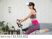 Купить «Young girl stay home in quarantine and go in for sports with virtual reality glasses. Woman exercise yoga while at home wearing virtual reality glasses», фото № 33533432, снято 4 апреля 2020 г. (c) Сергей Тимофеев / Фотобанк Лори