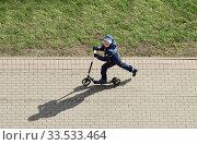 Купить «Мальчик катается на самокате», фото № 33533464, снято 10 апреля 2020 г. (c) Валерия Попова / Фотобанк Лори