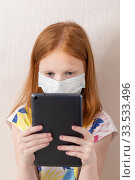 Купить «Adorable red haired girl wearing medicine mask for stop coronavirus outbreak. 8 years old girl look at tablet. Self isolation at home. Education from home. Vertical photo», фото № 33533496, снято 10 апреля 2020 г. (c) Evgenia Shevardina / Фотобанк Лори