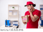 Купить «Young male courier delivering postbox to the office», фото № 33533916, снято 19 ноября 2019 г. (c) Elnur / Фотобанк Лори