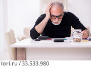 Old male retired in budget planning concept. Стоковое фото, фотограф Elnur / Фотобанк Лори