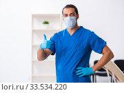 Купить «Young male doctor working in the clinic», фото № 33534220, снято 21 сентября 2019 г. (c) Elnur / Фотобанк Лори