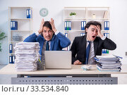 Two male colleagues unhappy with excessive work. Стоковое фото, фотограф Elnur / Фотобанк Лори