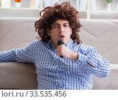 Купить «Funny man singing songs in karaoke at home», фото № 33535456, снято 29 марта 2017 г. (c) Elnur / Фотобанк Лори