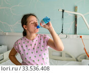 Pregnant girl in the hospital awaits her birth and drinks water from a bottle. Стоковое фото, фотограф Василий Кочетков / Фотобанк Лори