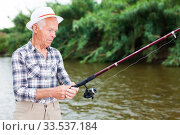 Mature man angling at riverside. Стоковое фото, фотограф Яков Филимонов / Фотобанк Лори