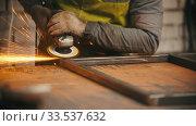 Купить «Man worker grinding the seams of an iron frame in the workshop - sparkles comes off the metal», видеоролик № 33537632, снято 29 мая 2020 г. (c) Константин Шишкин / Фотобанк Лори