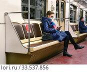 Москва. Женщина в медицинской  маске едет в вагоне метро (2020 год). Редакционное фото, фотограф Dmitry29 / Фотобанк Лори