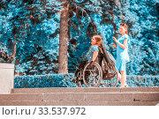 Купить «Russia, Samara, June 2019: a student girl walks with her friend to the disabled sitting in a wheelchair along the Volga River embankment on a sunny summer day.», фото № 33537972, снято 1 июня 2019 г. (c) Акиньшин Владимир / Фотобанк Лори