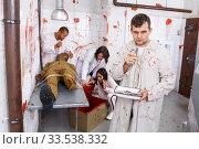 Focused guy in escape room with traces of blood. Стоковое фото, фотограф Яков Филимонов / Фотобанк Лори