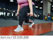 Купить «Overweight woman, exercise with dumbbells in gym», фото № 33539208, снято 28 декабря 2019 г. (c) Tryapitsyn Sergiy / Фотобанк Лори