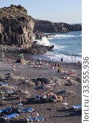 People rest on the Playa de Ajabo beach. Black volcanic sand is on Atlantic ocean coast line. Тенерифе, Канары, Испания (2016 год). Редакционное фото, фотограф Кекяляйнен Андрей / Фотобанк Лори