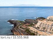 Купить «The La Gomera island is on horizon on the Atlantic ocean. Empty coastline of the Playa Paraiso. Tenerife, Canary islands. Spain», фото № 33555968, снято 5 января 2016 г. (c) Кекяляйнен Андрей / Фотобанк Лори