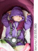 Sleeping baby portrait, lying inside of stroll fastened with safety belt, hands up. Стоковое фото, фотограф Кекяляйнен Андрей / Фотобанк Лори