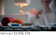 Купить «Young woman designer working with clothes and pins sitting by the sewing machine», видеоролик № 33556116, снято 6 июня 2020 г. (c) Константин Шишкин / Фотобанк Лори