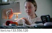 Купить «Young woman designer sewing decorative mask using a sewing machine», видеоролик № 33556120, снято 4 июля 2020 г. (c) Константин Шишкин / Фотобанк Лори