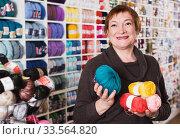 Positive mature female with colorful yarn in shop. Стоковое фото, фотограф Яков Филимонов / Фотобанк Лори