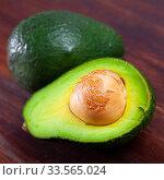 Купить «Close up of cut avocado with bone at wooden table», фото № 33565024, снято 11 июля 2020 г. (c) Яков Филимонов / Фотобанк Лори