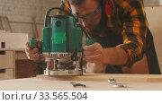 Купить «Carpentry industry indoors - man worker in protective glasses and headphones grinding a wooden item in the workshop», видеоролик № 33565504, снято 2 июня 2020 г. (c) Константин Шишкин / Фотобанк Лори