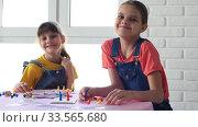 Две девочки играют в настольные игры и весело посмотрели в кадр. Стоковое видео, видеограф Иванов Алексей / Фотобанк Лори