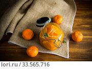 Купить «tangerine jam in a glass jar on a wooden table», фото № 33565716, снято 16 апреля 2020 г. (c) Peredniankina / Фотобанк Лори