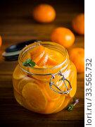 Купить «tangerine jam in a glass jar on a wooden table», фото № 33565732, снято 16 апреля 2020 г. (c) Peredniankina / Фотобанк Лори