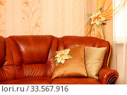 Brown leather sofa with beautiful pillows, a row a window with a curtain. Horizontal shot. Close up. The embroidery isn't a handiwork, this repetition of drawing on wall-paper. Стоковое фото, фотограф Zoonar.com/Sergey Chirkov / age Fotostock / Фотобанк Лори
