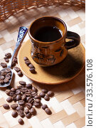 Cup of coffee on a wicker tray in a rustic style and coffee grains close-up. Стоковое фото, фотограф Яна Королёва / Фотобанк Лори