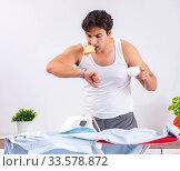 Купить «Young man ironing in the bedroom», фото № 33578872, снято 27 июня 2018 г. (c) Elnur / Фотобанк Лори