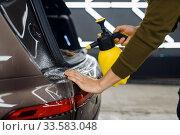 Купить «Worker wets rear bumper surface of car, detailing», фото № 33583048, снято 20 марта 2020 г. (c) Tryapitsyn Sergiy / Фотобанк Лори