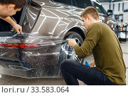 Купить «Specialists applies car protection film on bumper», фото № 33583064, снято 20 марта 2020 г. (c) Tryapitsyn Sergiy / Фотобанк Лори