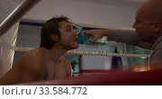 Caucasian coach giving water to caucasian athlete in boxing ring. Стоковое видео, агентство Wavebreak Media / Фотобанк Лори
