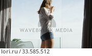 Купить «Caucasian woman looking at the sea in hotel room», видеоролик № 33585512, снято 13 мая 2019 г. (c) Wavebreak Media / Фотобанк Лори