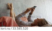 Caucasian woman sitting on couch in hotel room. Стоковое видео, агентство Wavebreak Media / Фотобанк Лори