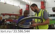 Workers discussing about a wheel. Стоковое видео, агентство Wavebreak Media / Фотобанк Лори