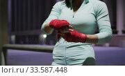 Купить «Young woman putting on ribbon», видеоролик № 33587448, снято 26 июня 2019 г. (c) Wavebreak Media / Фотобанк Лори