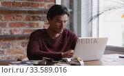 Купить «Mixed race man concentrated and working in his house», видеоролик № 33589016, снято 8 июля 2019 г. (c) Wavebreak Media / Фотобанк Лори