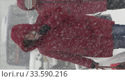 Vertical format video woman in red winter jacket walking sidewalk, hiding faces from snow storm during Pacific snow cyclone (2019 год). Редакционное видео, видеограф А. А. Пирагис / Фотобанк Лори