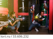 Happy young friends playing laser tag game with laser guns in. Стоковое фото, фотограф Яков Филимонов / Фотобанк Лори